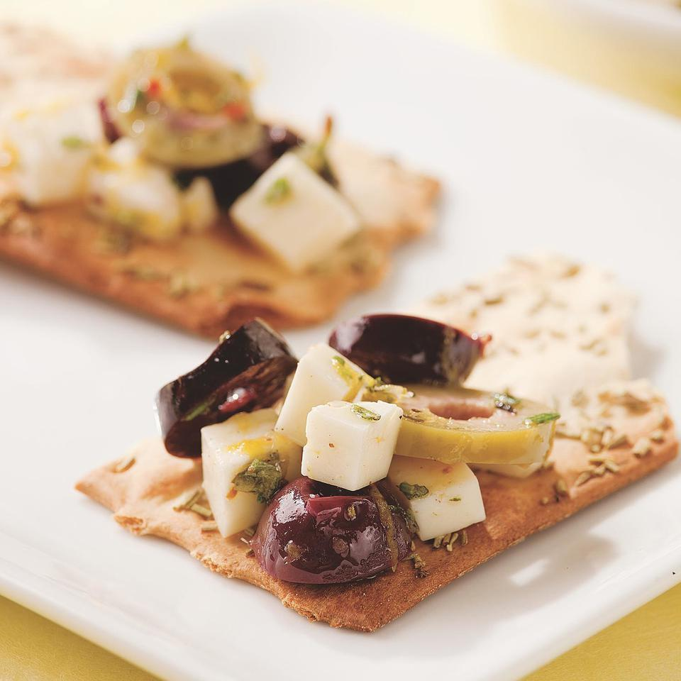 Olives and feta marinated with rosemary, lemon and garlic are great served on crisp flatbread-style crackers or warm slices of crusty baguette.