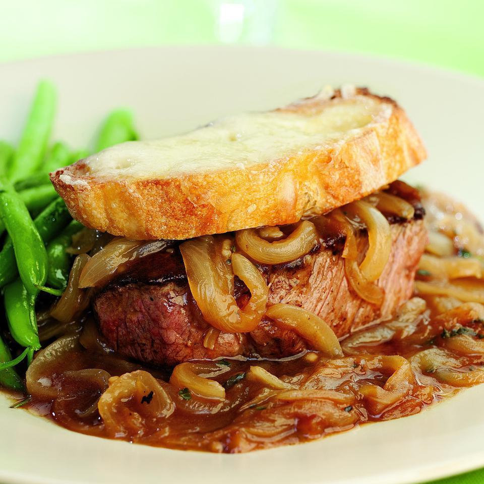 We took the comforting flavors of French onion soup and turned them into an easy bistro-style steak dinner. Tender filet mignon gets smothered with sweet caramelized onions and topped by a crispy, Swiss cheese–covered crostini. To double this recipe use 2 large skillets and prepare one 4-serving recipe in each. Serve with green beans and mashed potatoes with buttermilk and chives.