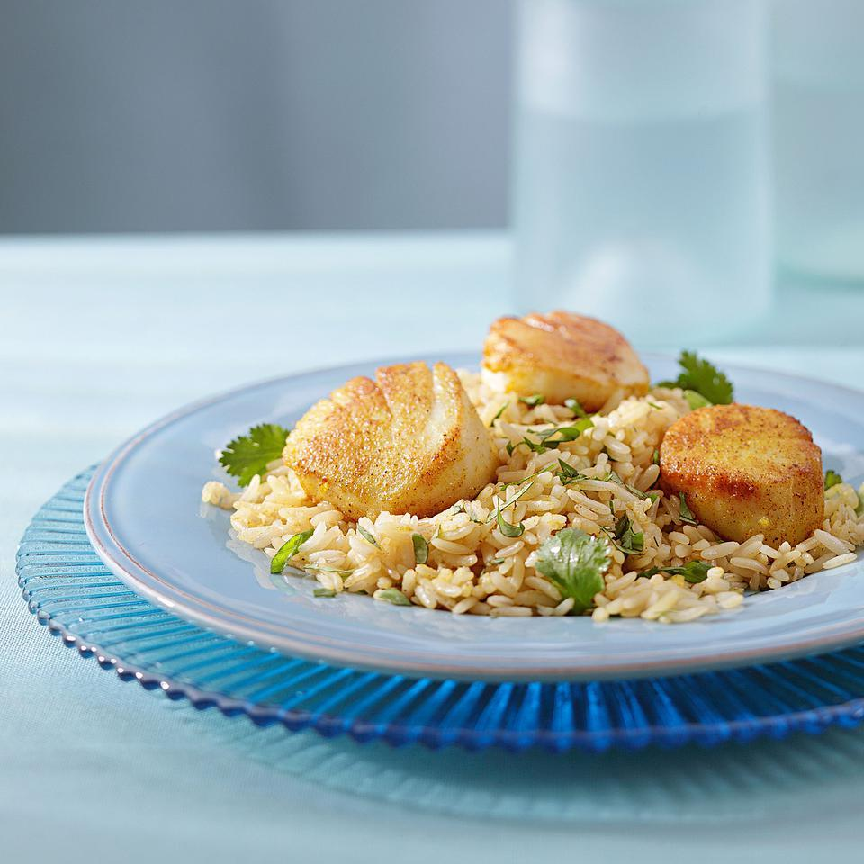 This recipe for two pairs curry-coated scallops and brown rice seasoned with cilantro, scallions and lemon. Serve with roasted carrots tossed with cumin and coriander. Source: EatingWell Magazine, March/April 2012