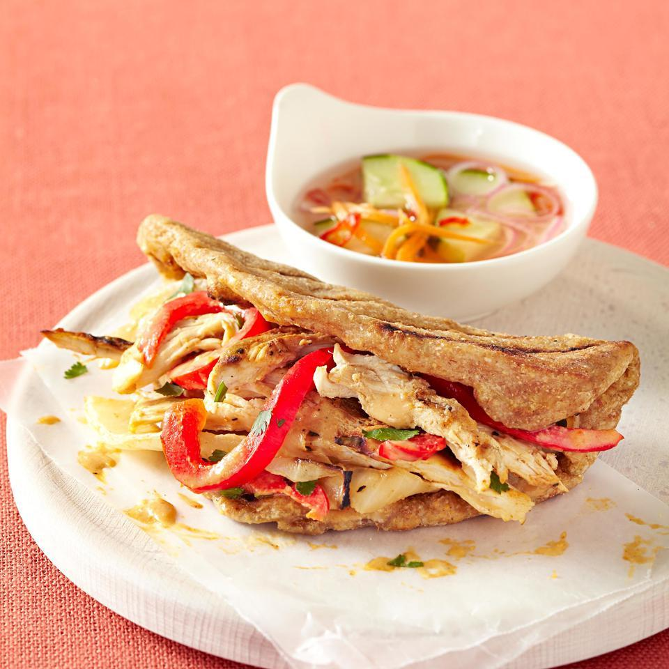 Juicy grilled chicken, onions and peppers combine with a Thai-inspired sauce in this chicken sandwich recipe. We love how the flatbreads made from whole-wheat dough sop up the extra sauce. If you have one large (12-ounce) chicken breast instead of two smaller (6-ounce) ones, cut it in half horizontally before grilling so the chicken cooks in the time specified in this recipe. Source: EatingWell Magazine, September/October 2012
