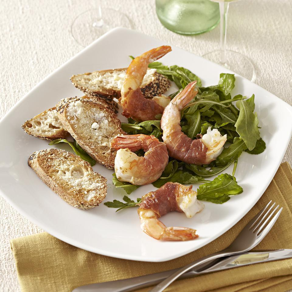 This recipe for jumbo shrimp wrapped in thin strips of prosciutto and served on a lemony bed of arugula is a practically effortless recipe for two. Wrap your shrimp and make the dressing ahead of time, and you'll have dinner on the table even faster. Serve with toasted whole-wheat baguette sprinkled with Parmesan cheese. Source: EatingWell Magazine, November/December 2012