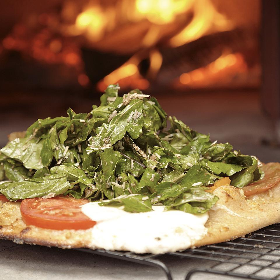 This Italian-flag-inspired Margherita pizza recipe is topped with juicy tomatoes and slices of fresh mozzarella. What could make it better? Adding a salad on top of the pizza to make a pizz'alad. In this case the Margherita pizza is topped with a salad of arugula, basil and parsley tossed with a tangy balsamic vinaigrette. Bread flour gives the pizza crust a crisp and sturdy structure, but all-purpose flour works well in its place. For a gluten-free pizza crust variation, see Tips.Source: EatingWell Magazine, July/August 2013