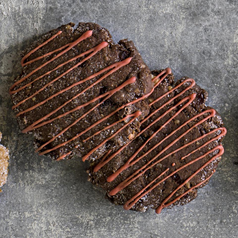 This healthy chocolate cookie recipe makes thin, sugar-kissed cookies flavored with dried cranberries and hazelnuts. The cookies are drizzled with homemade natural red icing, but if you prefer white icing, omit the natural red dye.