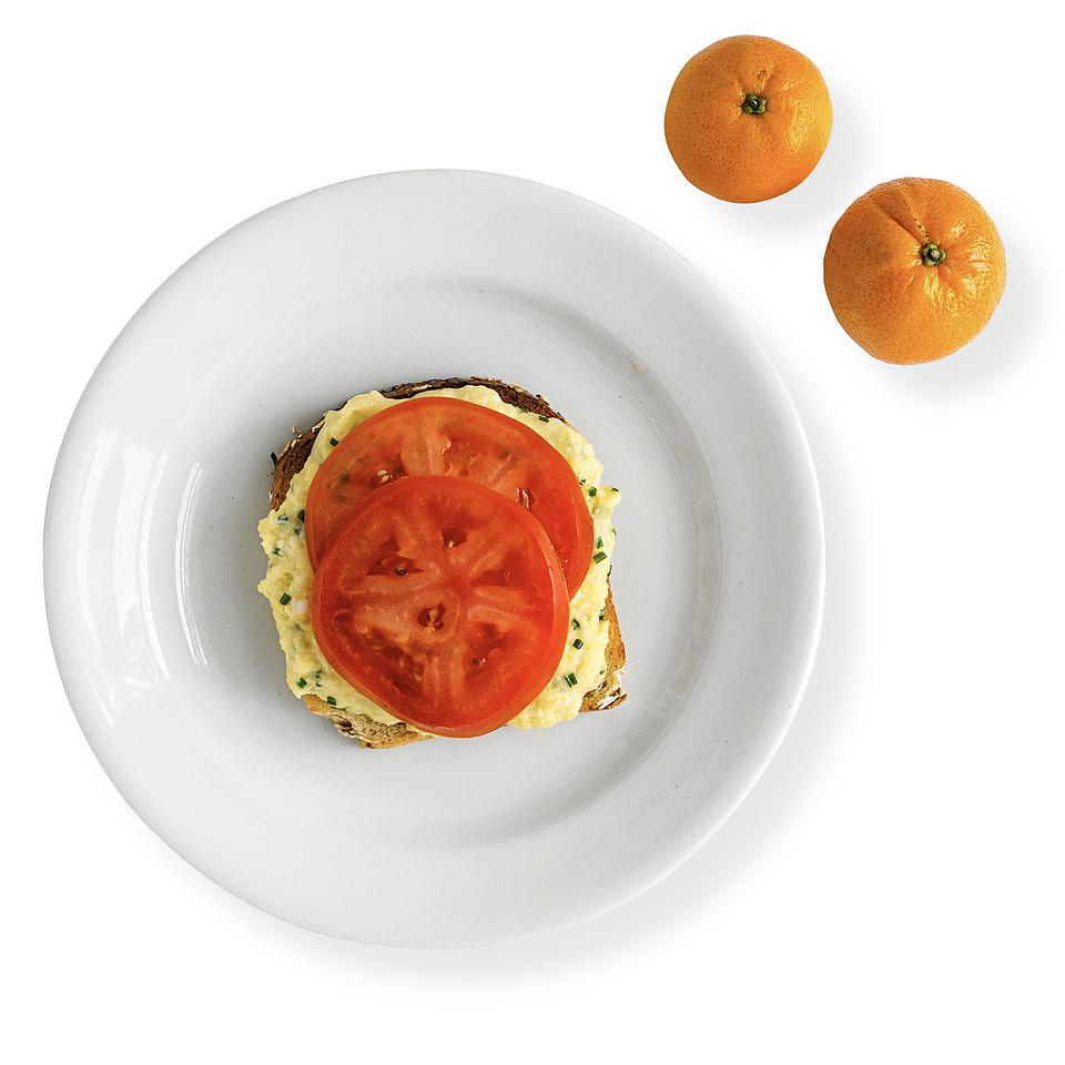 In this healthy open-face egg sandwich recipe, Swiss cheese and chives are gently folded into the beaten egg and layered with tomato on multigrain toast.