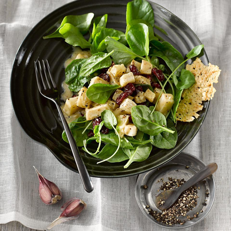 The big flavor of sherry vinegar mixed with mustard, oil and garlic in the dressing for this healthy spinach salad recipe serves a dual purpose: marinade for the roasted celery root and a dressing for this side salad. Little rounds of crunchy Parmesan crisps look fancy, but are easy to make and add a perfect textural contrast and salty counterpart to the earthy and spicy greens and sweet-tart cranberries.