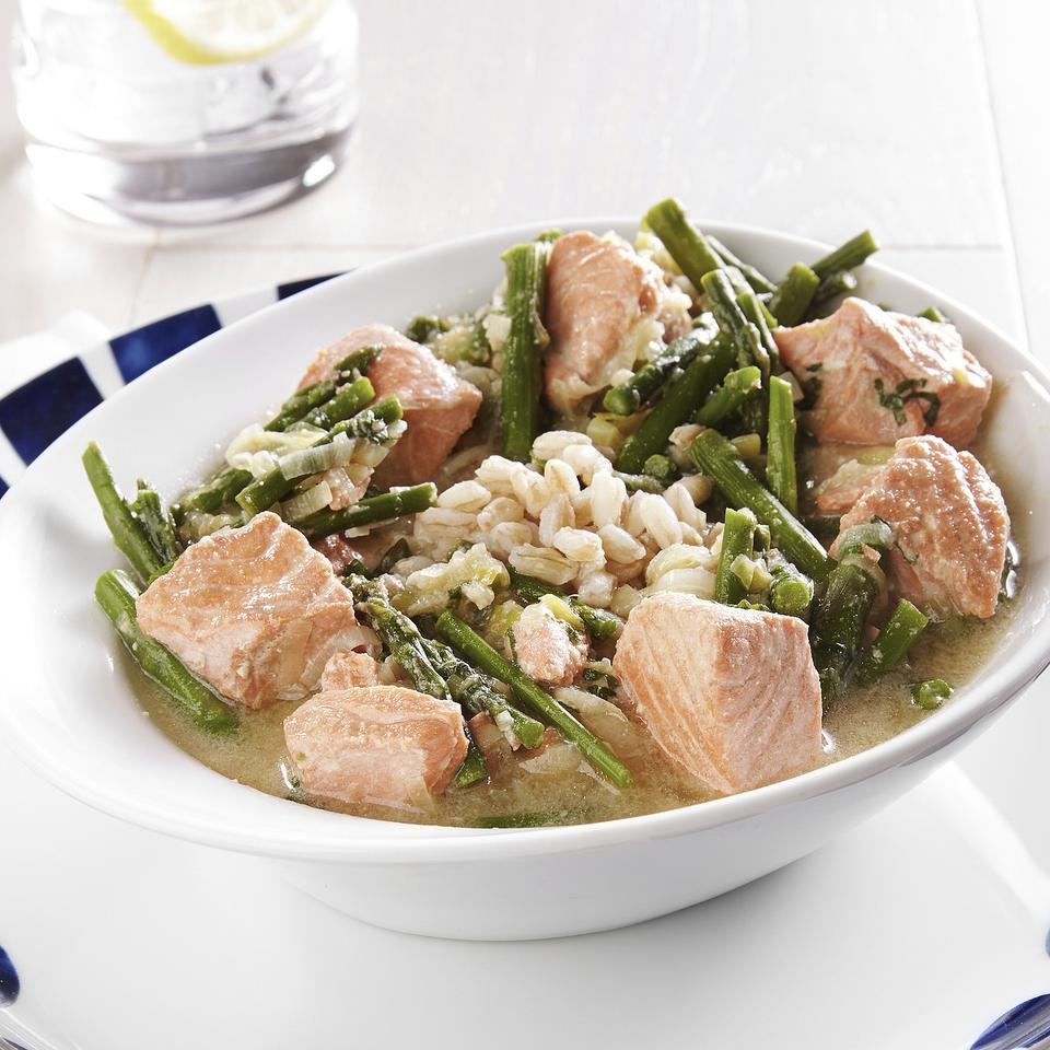 """In this farro and salmon recipe, salmon is poached in a miso-infused broth with bites of tender asparagus and sautéed leeks. If you use farro that's labeled """"pearled,"""" a faster-cooking farro, to make this recipe, start with a full cup of grains and reduce the cooking time to 15 minutes. To clean the leeks, trim off the green tops and white roots and split lengthwise. Place in a large bowl of water and swish around to release any sand or soil. Repeat until no grit remains."""