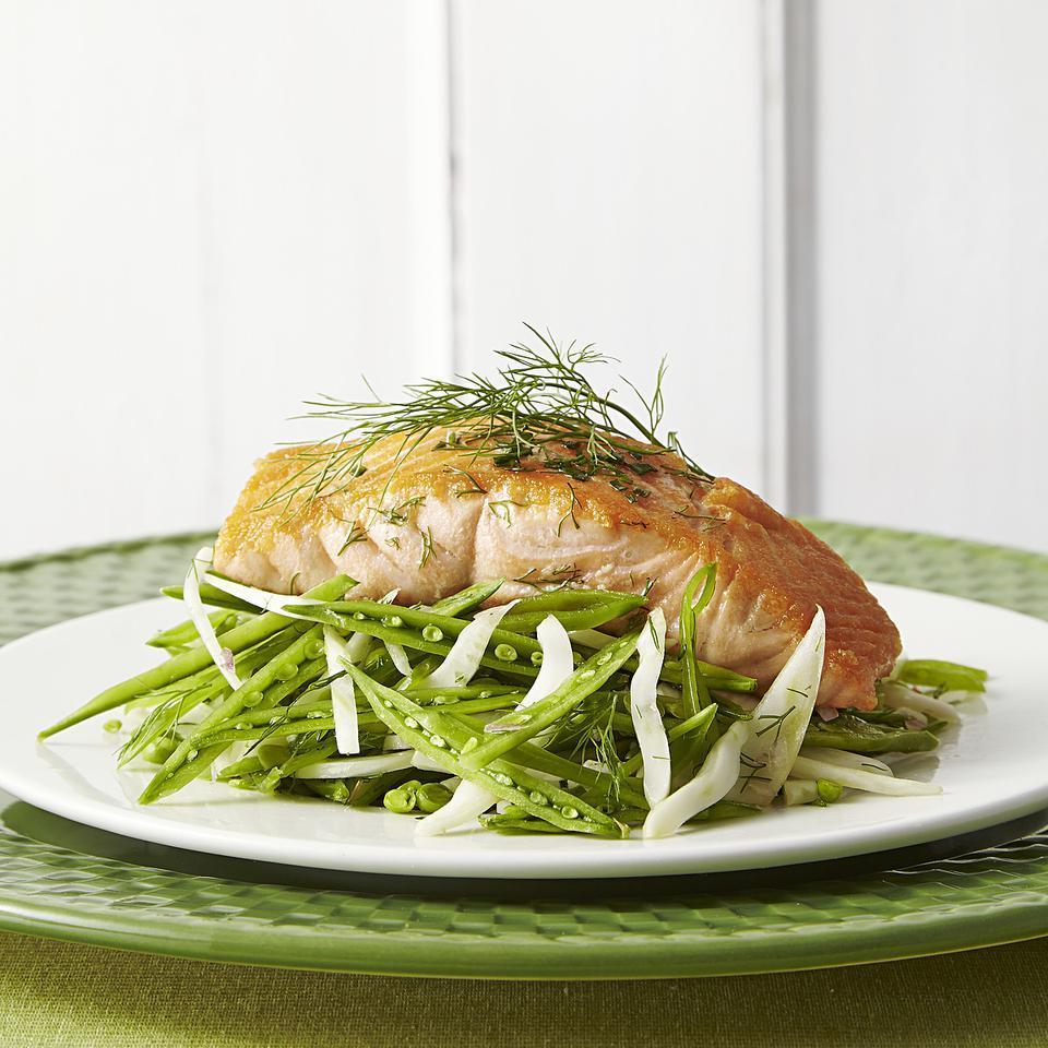 A light and summery snap pea-and-fennel slaw makes a crisp bed for the seared salmon in this healthy dinner recipe. The delicate fennel fronds add more mild licorice flavor to the dish.