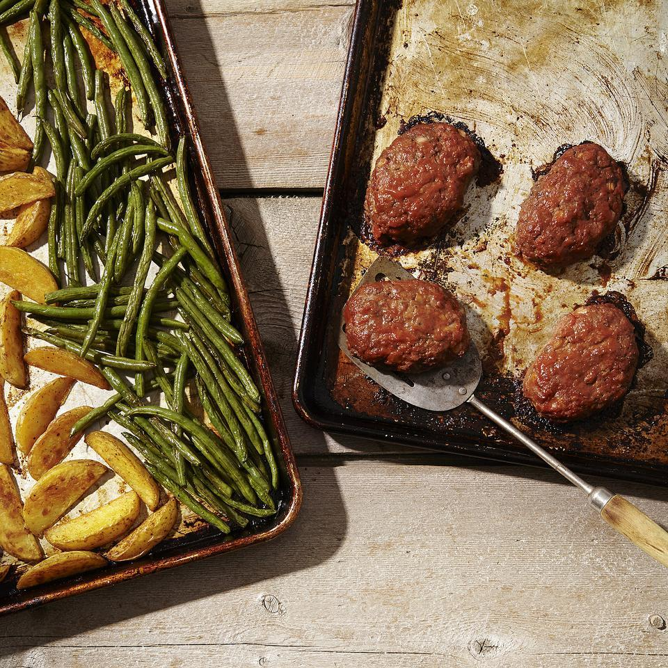 This healthy meatloaf recipe and side dishes are all made in the oven on two sheet pans so that everything's ready for the dinner table at the same time. The potatoes go into the oven first to start roasting while the mini meatloaves and green beans are prepped and added to the oven partway through. Source: EatingWell Magazine, September/October 2014