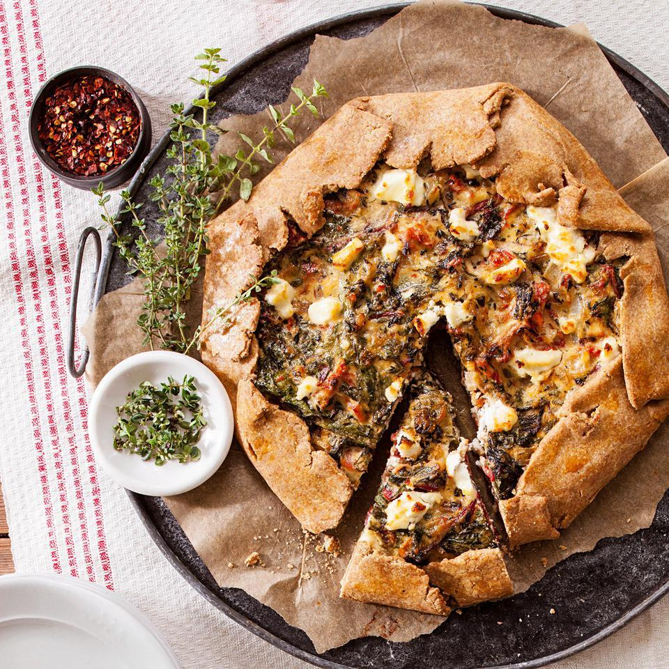 This free-form vegetarian galette, filled with caramelized onions, chard, plenty of fresh herbs and topped with rich goat cheese, can be served as an impressive vegetarian entree or as a side dish. This galette recipe is perfect if you're intimidated by working with dough. Don't worry about getting the circle perfectly round, as you're going to be folding it over the edges of the filling anyway.