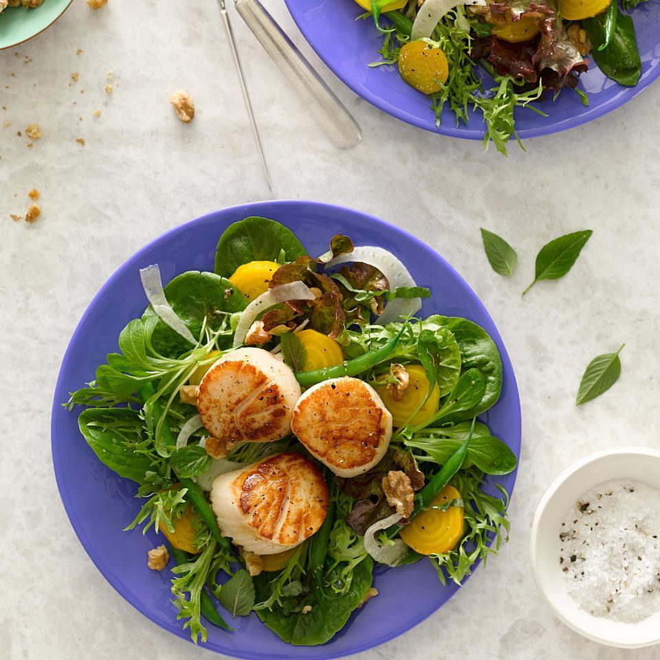 Lemony seared scallops and a walnut vinaigrette top this healthy dinner salad. When shopping for scallops, avoid those treated with sodium tripolyphosphate (STP); it can make them mushy and the scallops won't brown properly. Some scallops have a small white muscle on the side; remove it before cooking. Source: EatingWell Magazine, July/August 2015