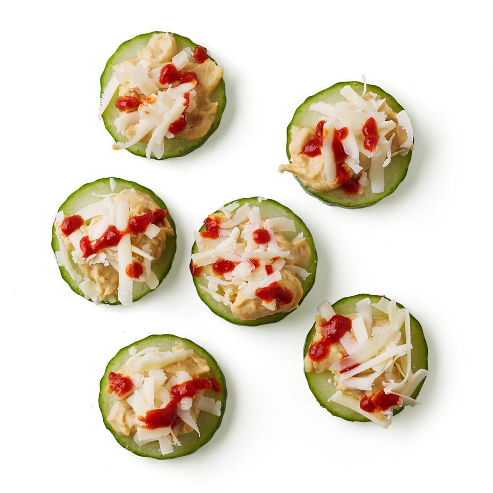 This quick, gluten-free snack recipe tops cucumbers with hummus, cheese and a hit of hot sauce.