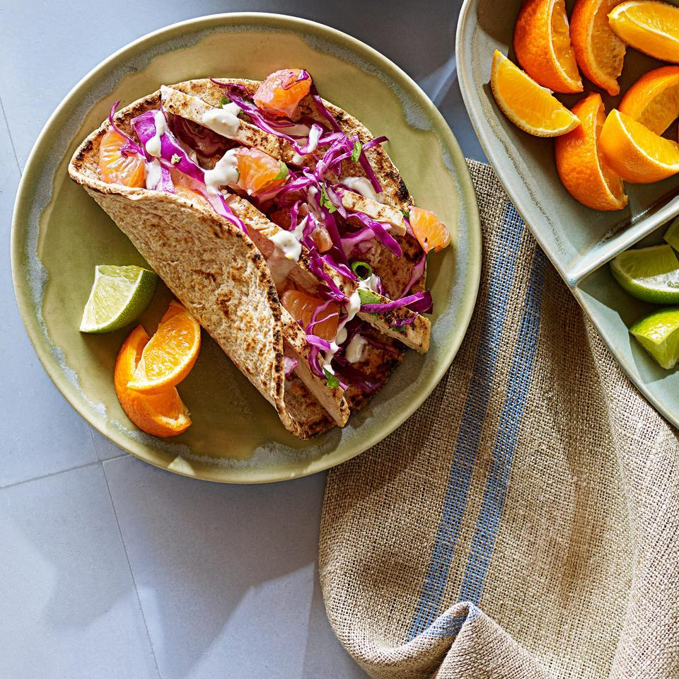 This spicy chicken taco recipe gets fresh orange flavor from both the crema and crunchy slaw toppings. Serve with tortilla chips and ice-cold beer.