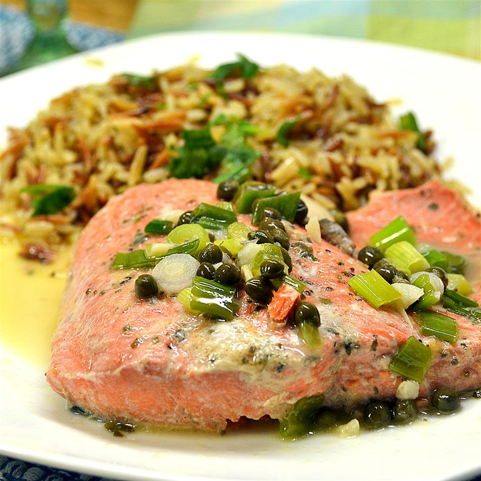 """Another easy but impressive dinner, salmon filets are poached in lemon juice and chicken bouillon, then topped with butter and capers. """"This is a delicious, creative way to serve salmon. You can serve the salmon on a bed of cooked noodles 鈥� I enjoy fettuccine 鈥� or on its own with a side of vegetables,"""" Ann says."""