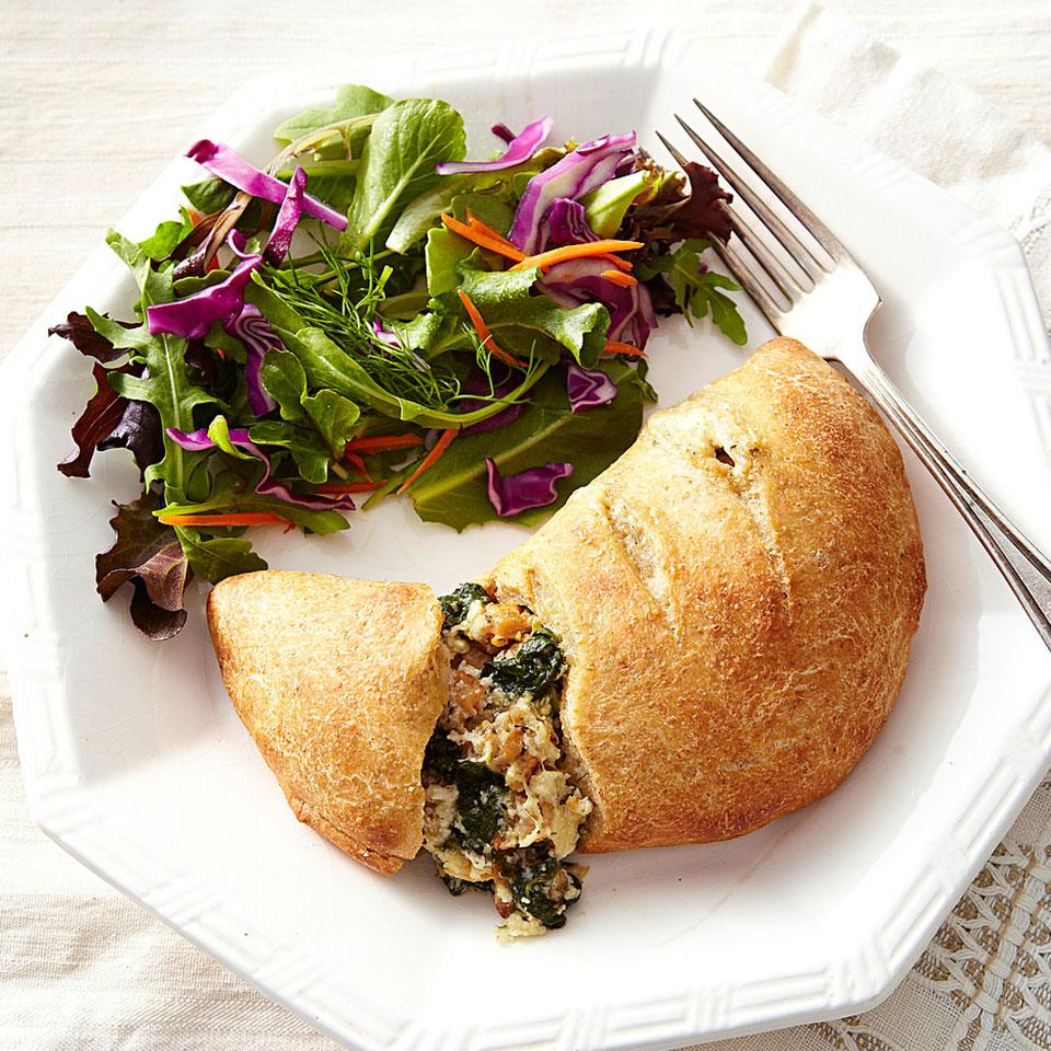 A typical calzone packs almost 800 calories and 25 grams of saturated fat. In this healthier calzone recipe, we use lean chicken sausage to keep fat in check and add nutrient-rich spinach to bulk up the filling without adding calories. Serve with marinara sauce for dipping.
