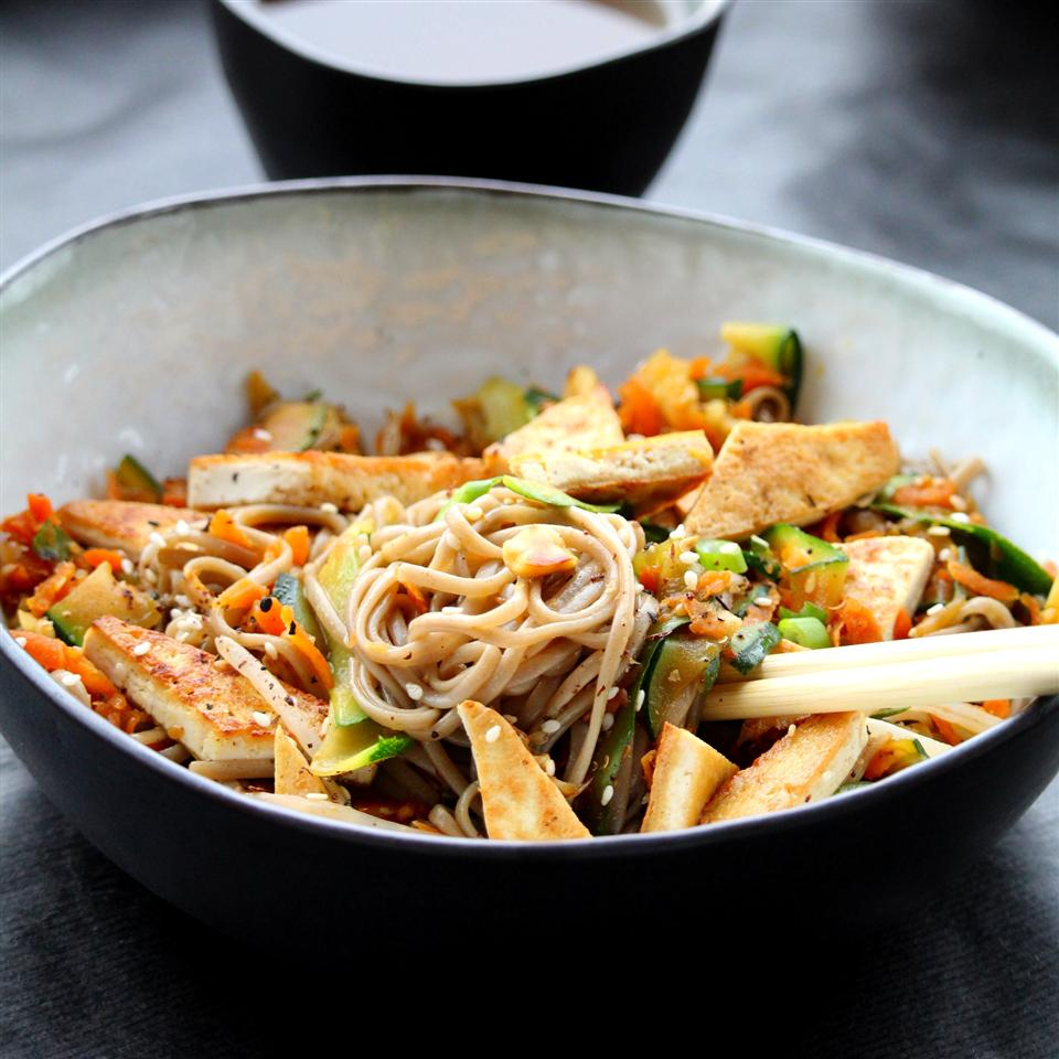 Brightly colored vegetables with a tamarind, ginger, and garlic sauce are tossed with baked tofu triangles and served over bi-colored soba noodles with sesame and peanut crunch. The tamarind gives this dish a beautiful color and tangy flavor.