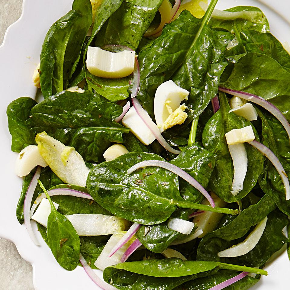 Belgian endive and slices of hearts of palm dress up this quick but classy spinach salad recipe, and the bright lemon-tarragon vinaigrette complements the greens with citrusy zing.