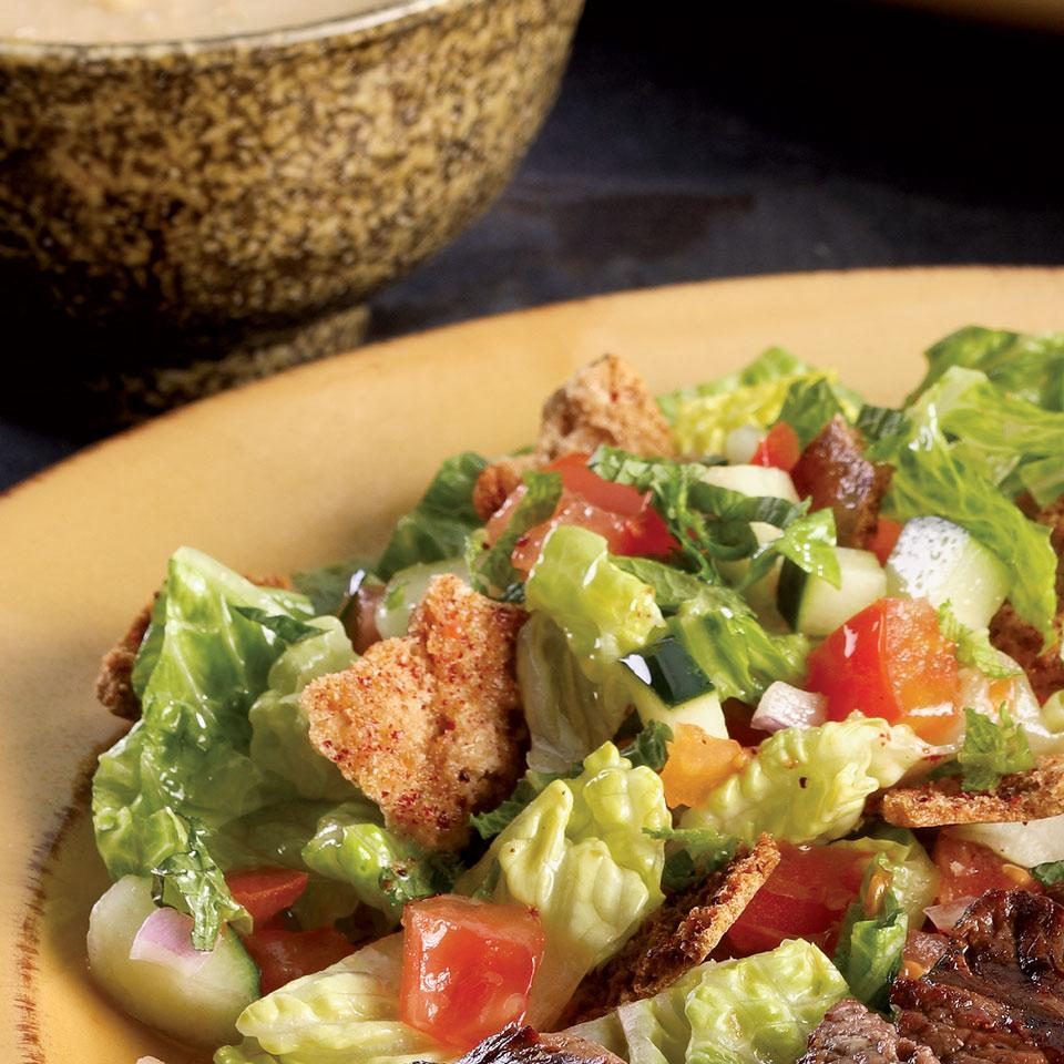 Fattoush is a popular salad in Lebanon made with mixed greens, a lemony vinaigrette and pita bread pieces. Toasting the pita adds crunch and a sprinkle of ground sumac--which grows wild all over Lebanon--adds depth. Let the salad sit for a bit to let the pita soak up the lemony dressing.
