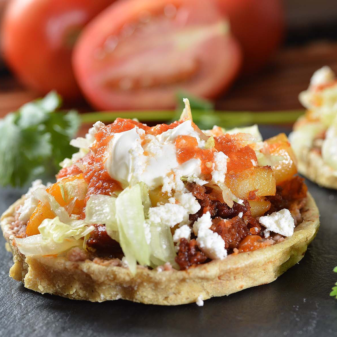This traditional Mexican dish has unique regional variations. Every sope is anchored by a thick fried-masa base. Regional Mexican versions have their own signature toppings, but you can create your own one-of-a-kind sope with your favorite combination of Mexican-style meats, vegetables, refried beans, cheeses, lettuce, salsa, and sour cream.