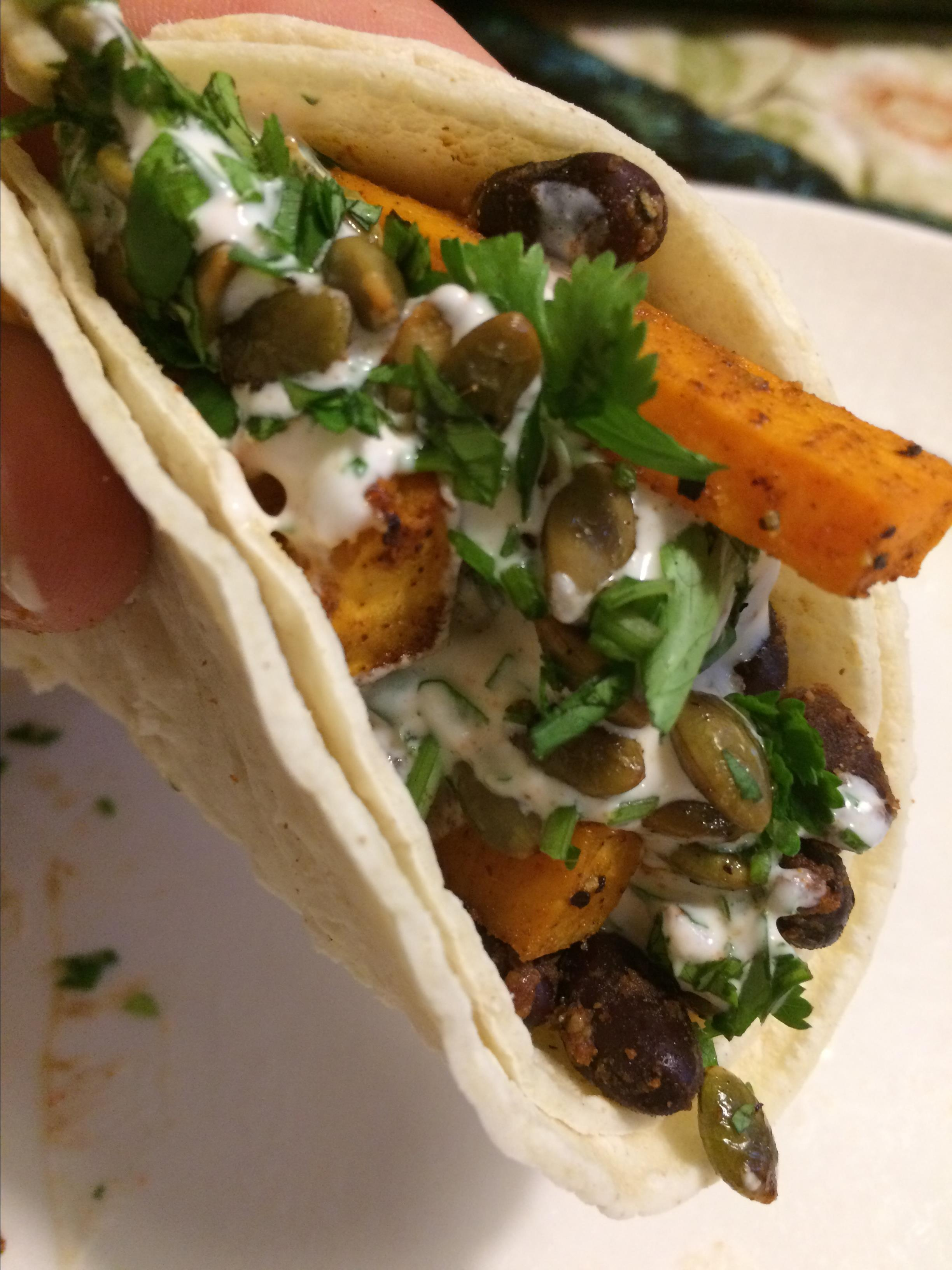 """Ready in 45 mins                           Super fresh and flavorful vegan tacos topped with spicy black beans and sweet potatoes and finished with a creamy cilantro-lime sauce. """"A fresh, subtle vegan take on tacos, sure to satisfy your comfort food craving!"""" says Ryan and Marissa."""