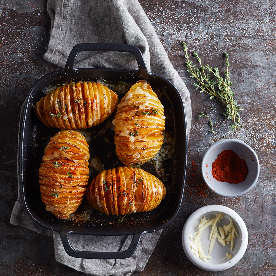 Hasselback potatoes are the perfect side dish for people who love crispy potato-chip-like slices as well as the tender interior of a baked potato. Simple to prepare, these hasselback potatoes look impressive and decadent with melted Cheddar cheese and a sprinkle of paprika on top.