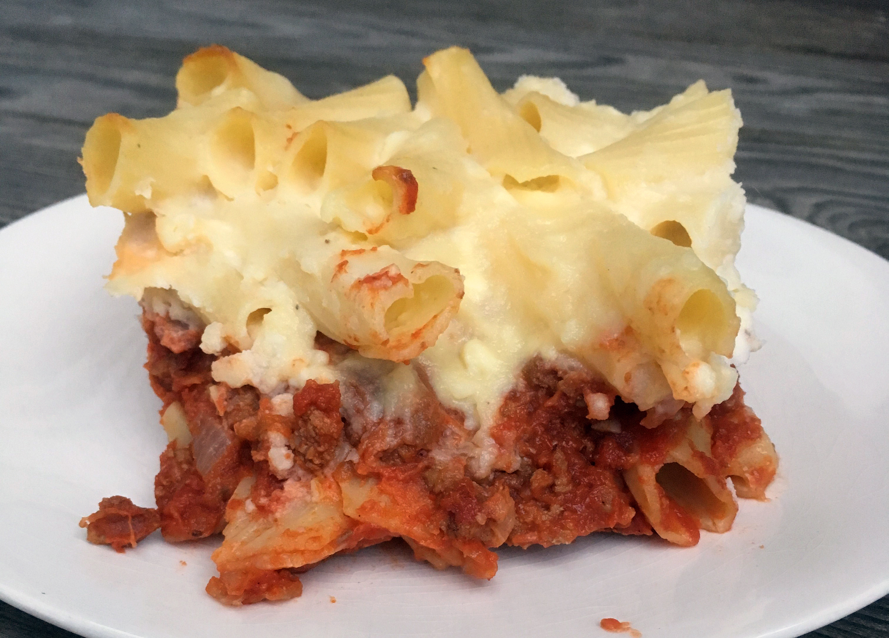 Spiced ground lamb with roasted eggplant, tomato sauce, and penne pasta is topped with a layer of rich, feta cheese sauce mixed with penne and baked to make this twist on the traditional Greek dish. Similar to lasagna, it might require a bit of effort but your family will thank you!
