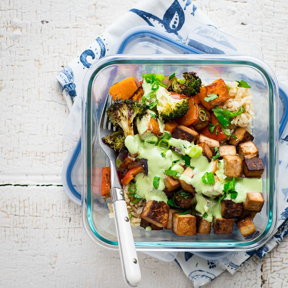 A healthy and satisfying vegan lunch for one, featuring roasted butternut squash, broccoli, peppers and onions with simple brown rice, lime-marinated tofu and creamy cashew tahini sauce. Source: EatingWell.com, December 2017