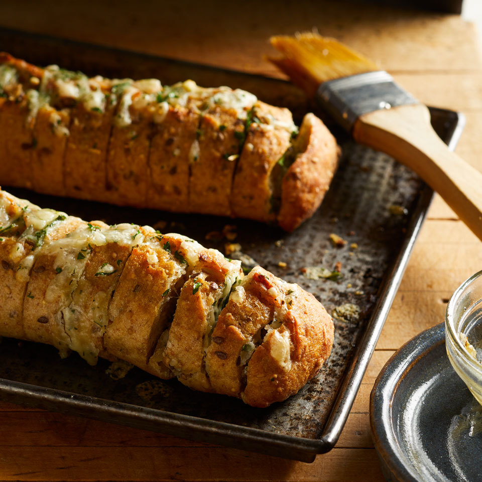 Potatoes were first to benefit from the Hasselback techinique—making thin slices crosswise toward the bottom of the vegetable, but not all the way through, so the potato becomes fanned, seasoned and baked until crisp. Here we've adapted the concept to garlic bread and updated it with cheese for an easy and completely mouthwatering cheesy bread side dish.