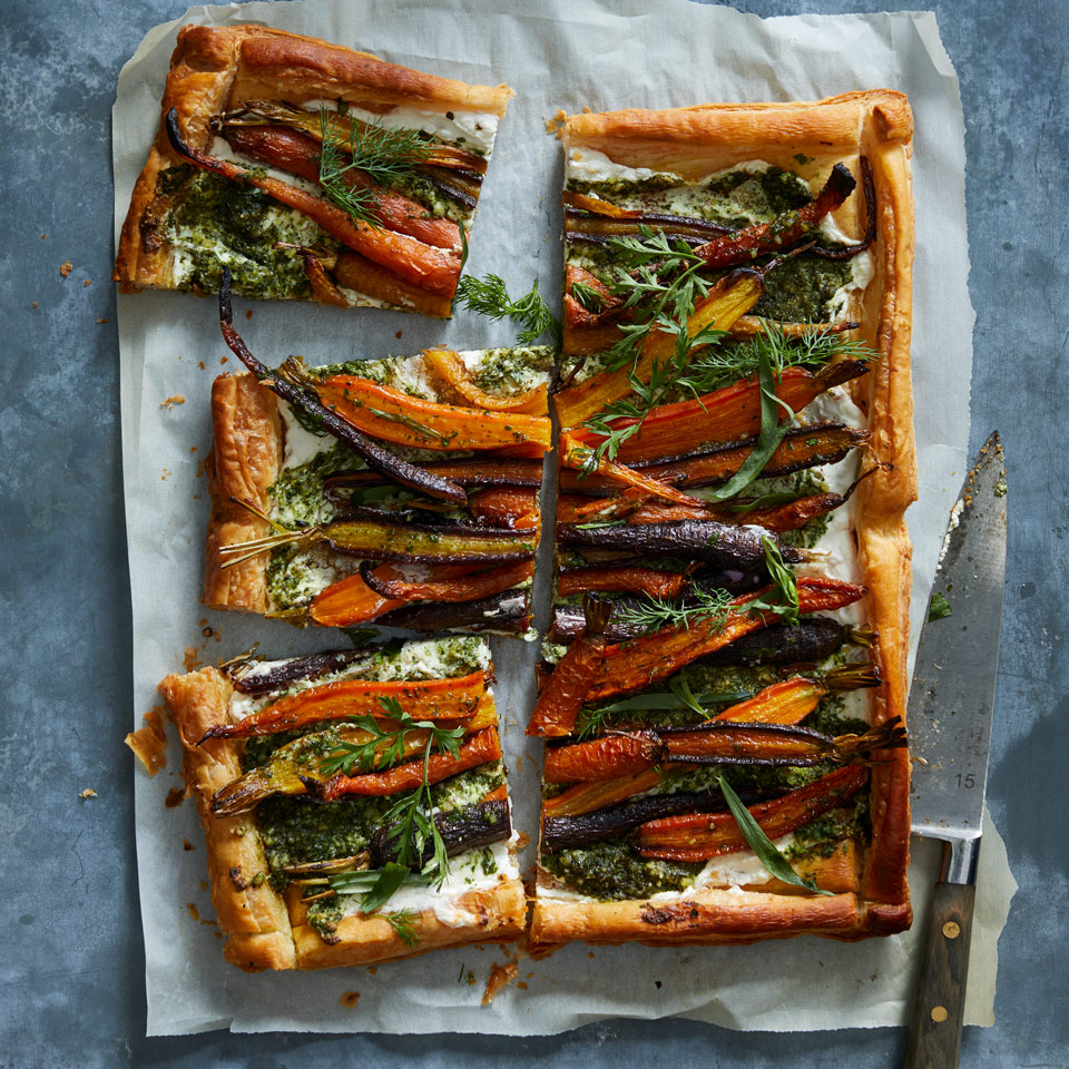 In this vegetarian main-dish recipe, you use the entire carrot from root to greens, so there's less waste. Roasted carrots are layered on top of a creamy ricotta base with pesto made using the green tops from carrots. Untrimmed carrots can be tough to find, but when you do, cut off the tops and store them separately or they'll draw moisture from the carrots. If you don't have carrot greens, use 1 cup of parsley instead.