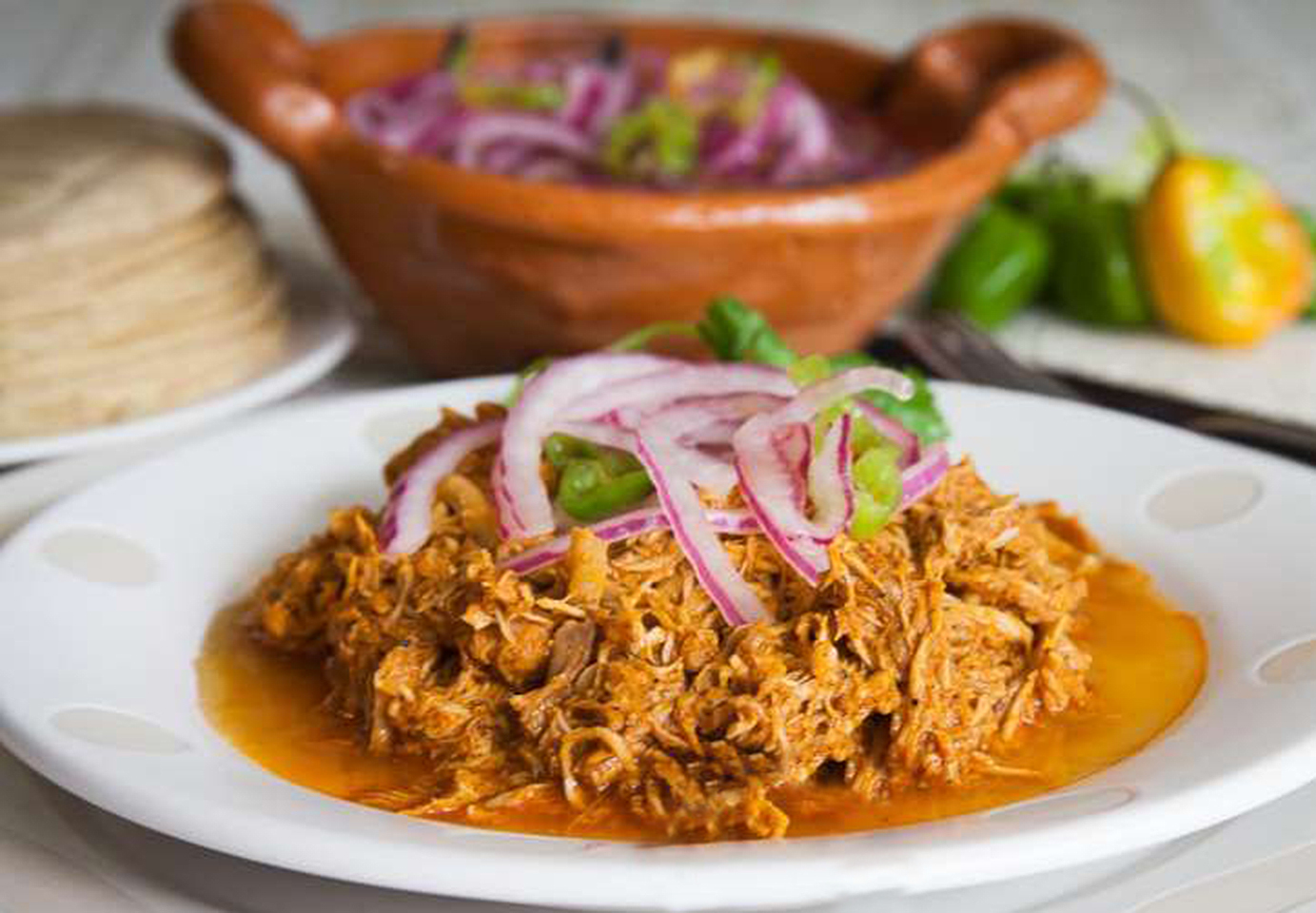 """Cochinita Pibil is a traditional Mexican version of pulled pork. """"This cochinita pibil recipe is straight from Mexico,"""" says Chef Gaby Cervello. """"Pork shoulder is cooked in a spicy red annatto paste and orange juice sauce, then shredded and served with habanero sauce."""""""