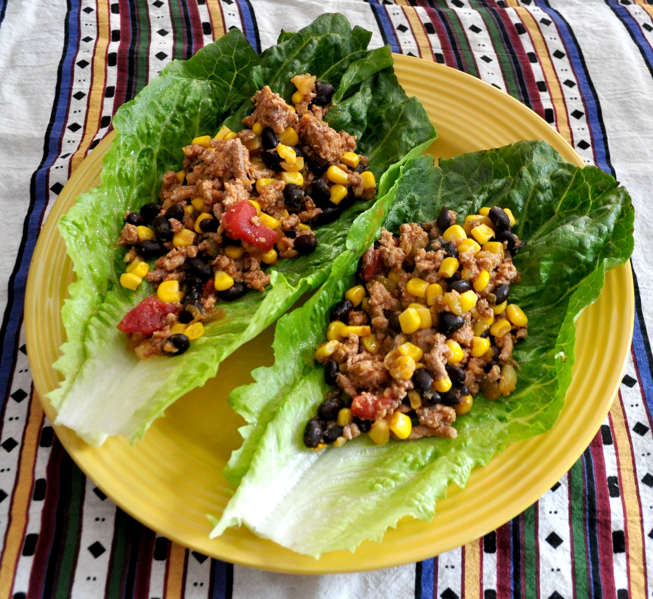 Corn, black beans, diced tomatoes, ground turkey, and taco seasonings are simmered and served wrapped up in large leaves of romaine.