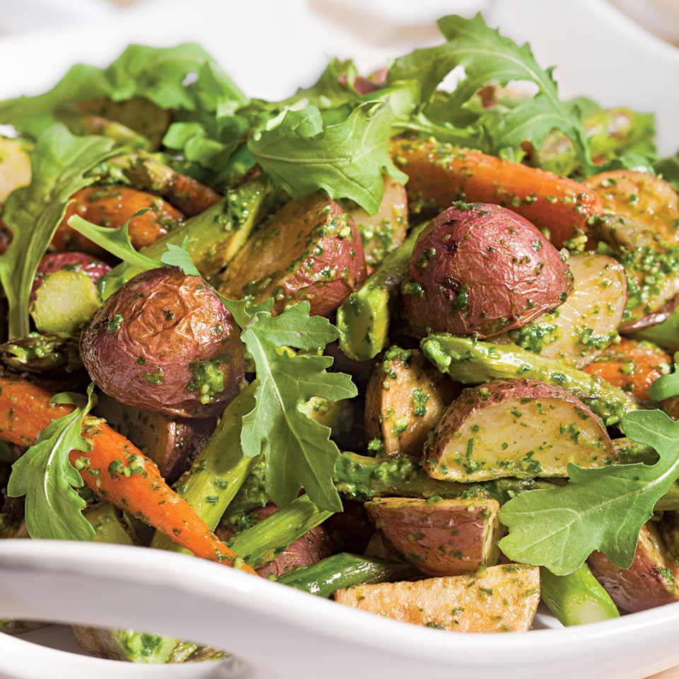 These roasted vegetables tossed with arugula pesto are an easy side for a dinner party. Try serving them with a roasted leg of lamb. If you can find beautiful, freshly harvested small carrots, they'll look and taste the best in this dish.