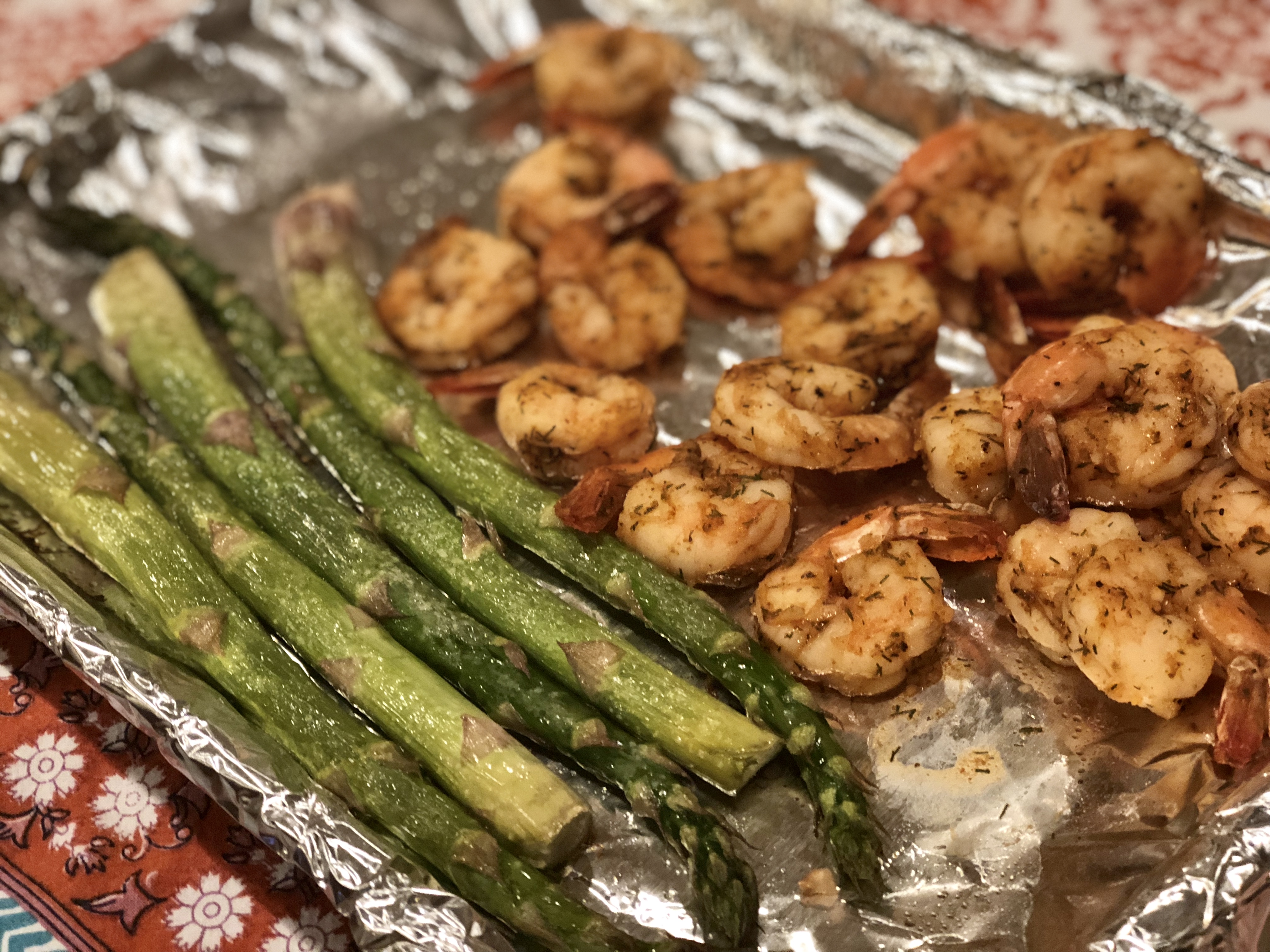 """Drizzle olive oil over asparagus spears, sprinkle with garlic, and arrange on one side of the pan, with shrimp on the other side, and top with olive oil and smoked paprika. Top asparagus and shrimp with cubed butter, bake, and drizzle with lemon juice. """"Have dinner ready in less than 30 minutes with this quick and easy one-pan roasted lemon butter shrimp and asparagus seasoned with garlic,"""" says Fioa."""
