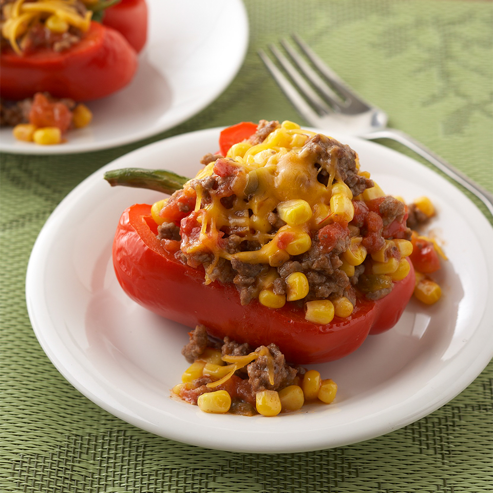 Sweet bell peppers are simmered to tenderness with ground beef, corn, and Mexican-style seasonings, stuffed, then topped with goat cheese for a hearty dinner that doesn't need an oven.