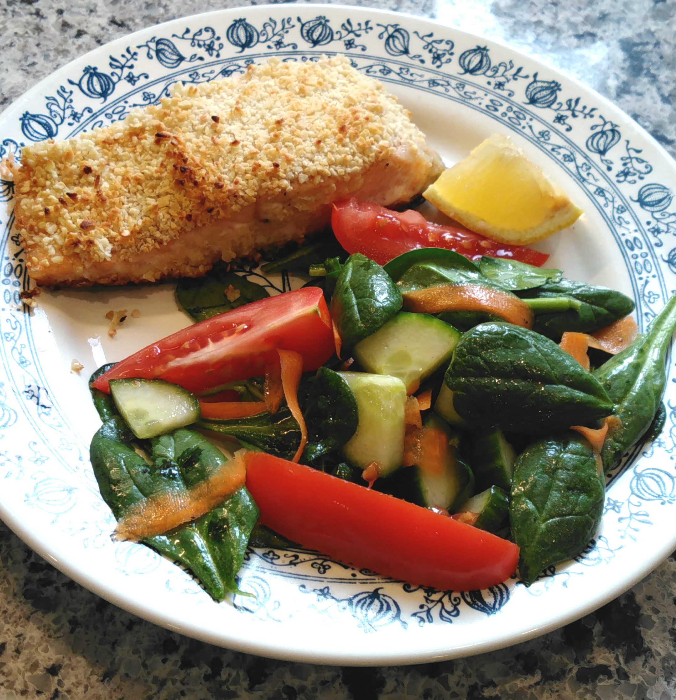 This baked salmon recipe has a baby spinach and cherry tomato side salad built right in. It makes a quick and easy weeknight dish for four.