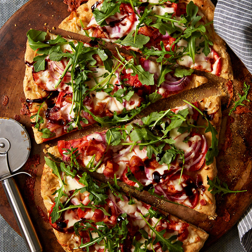 This homemade pizza riffs on the classic BLT sandwich, with crisp bacon, thin roma tomatoes and fresh arugula on top of a whole-wheat pizza crust.