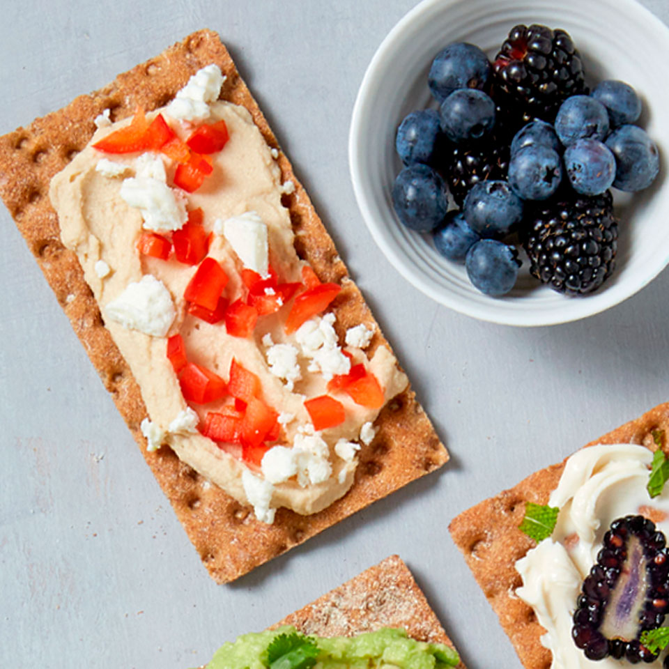 A savory topping of feta cheese, hummus, and sweet bell pepper make this super-easy, tasty crispbread snack a perfect munch for the long, warm days of summer. Source: Diabetic Living Magazine, Summer 2018