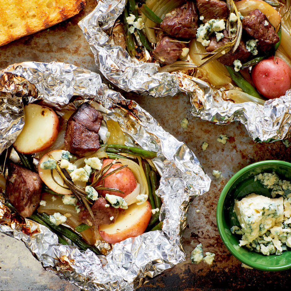 Steak and potatoes are a classic combo on the grill. We have taken the concept one step further by adding green beans and rosemary, and wrapping everything in a packet to make a complete meal. A sprinkling of blue cheese just before serving is the perfect finish for this steak-house special. Source: EatingWell.com, May 2018