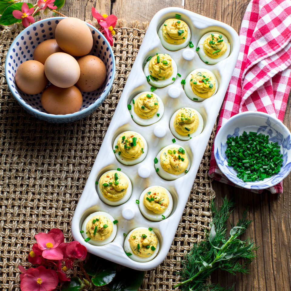 These eggs are perfect for a picnic because they're so portable. Instead of cutting them in half lengthwise, we just cut the tops off so they can stand upright in an egg carton for easy filling, transport and storage. We swapped in Greek yogurt for the traditional mayo to save calories.