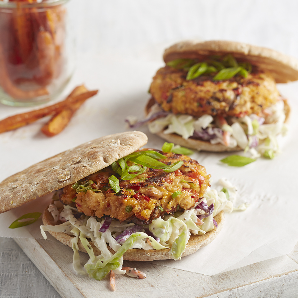 Salmon burgers on toasted rolls are served with tasty coleslaw and roasted carrots for a budget-friendly meal with plenty of vegetables.