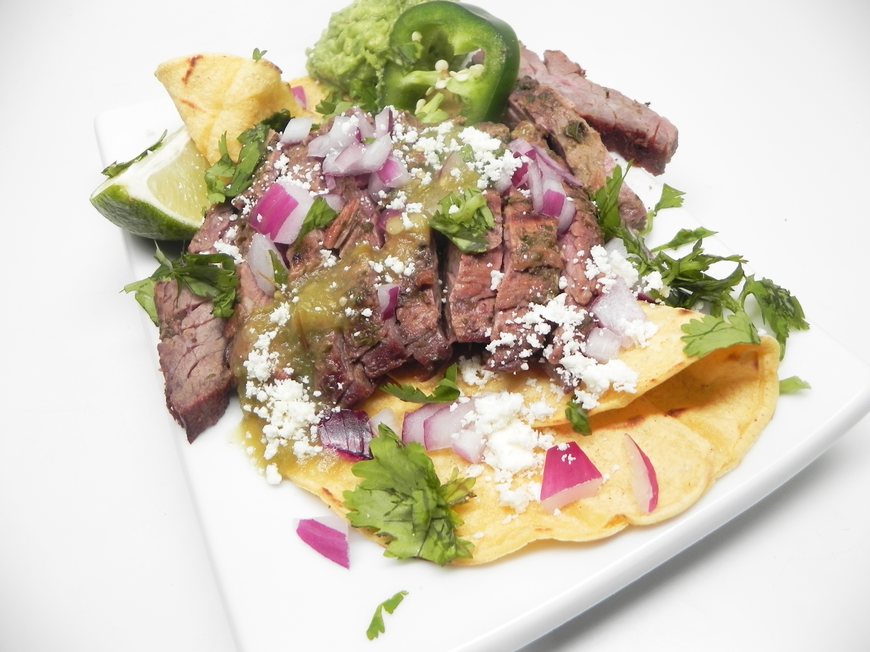 """""""In this true Mexican carne asada recipe, skirt steak is marinated in a cilantro-beer sauce and grilled (asada) to perfection,"""" says Crema. """"Serve with a side of drunken beans and corn tortillas. If preferred, substitute flank steak for the skirt steak."""""""