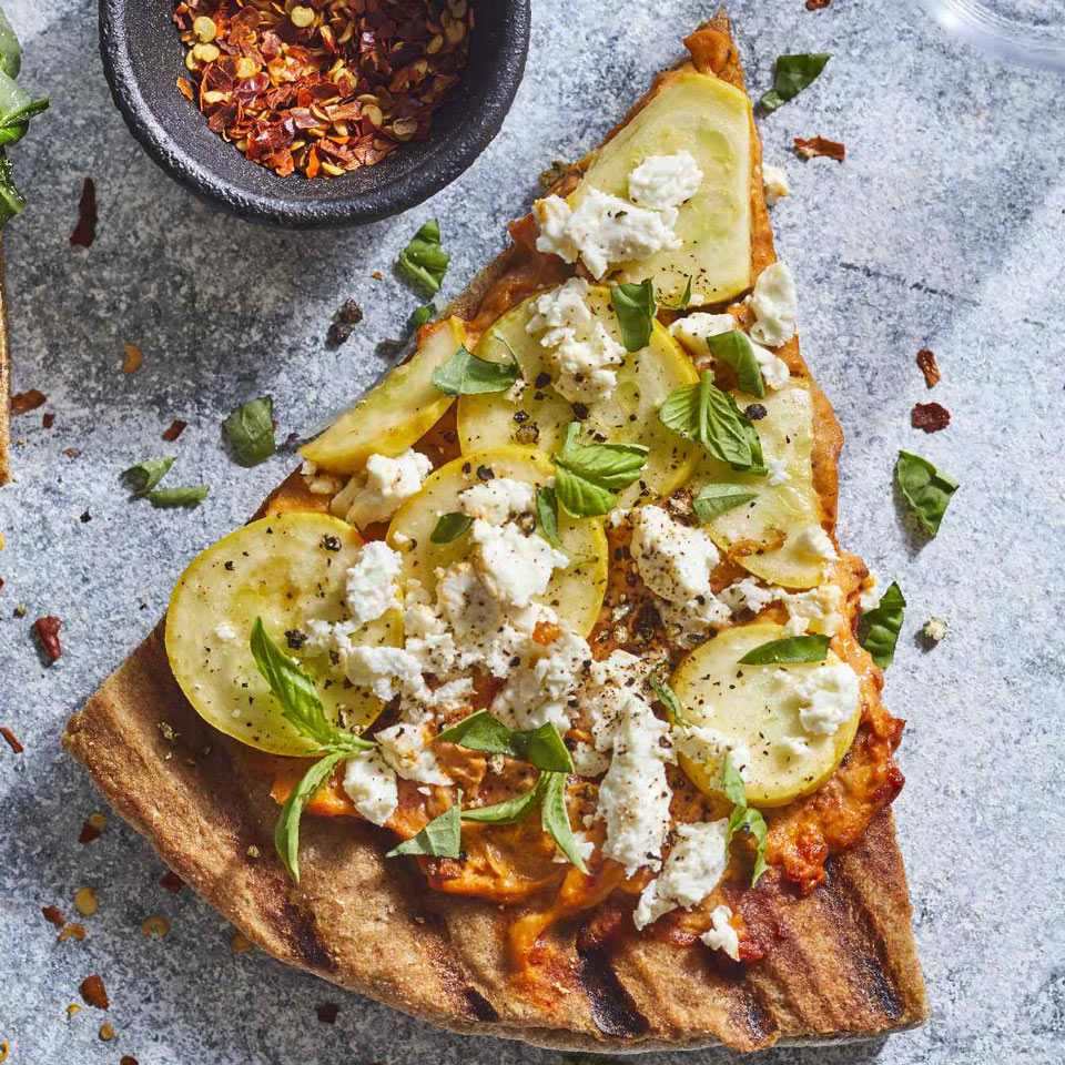 Spreading roasted red pepper hummus on this easy grilled pizza makes a fast and easy base for tender summer squash and salty chunks of feta. Best of all? This healthy pizza is ready in 20 minutes. Source: EatingWell Magazine, May/June 2018