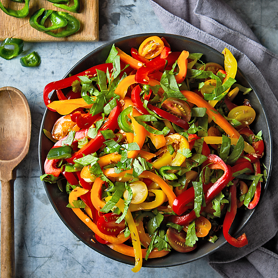 This sweet and tangy salad is chock full of peppers, onions, tomatoes and spinach that have been marinated in a mixture of toasted cumin seeds, lime juice and honey. It's the perfect addition to your next taco night.
