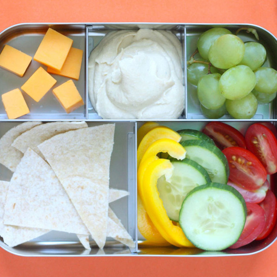 Pita wedges and crudité with hummus make a satisfyingly simple lunch box. We round out this Mediterranean-inspired snack lunch with cheese and fruit. If your child likes olives, sprinkle some into the veggie dippers. Source: Eatingwell.com, August 2018