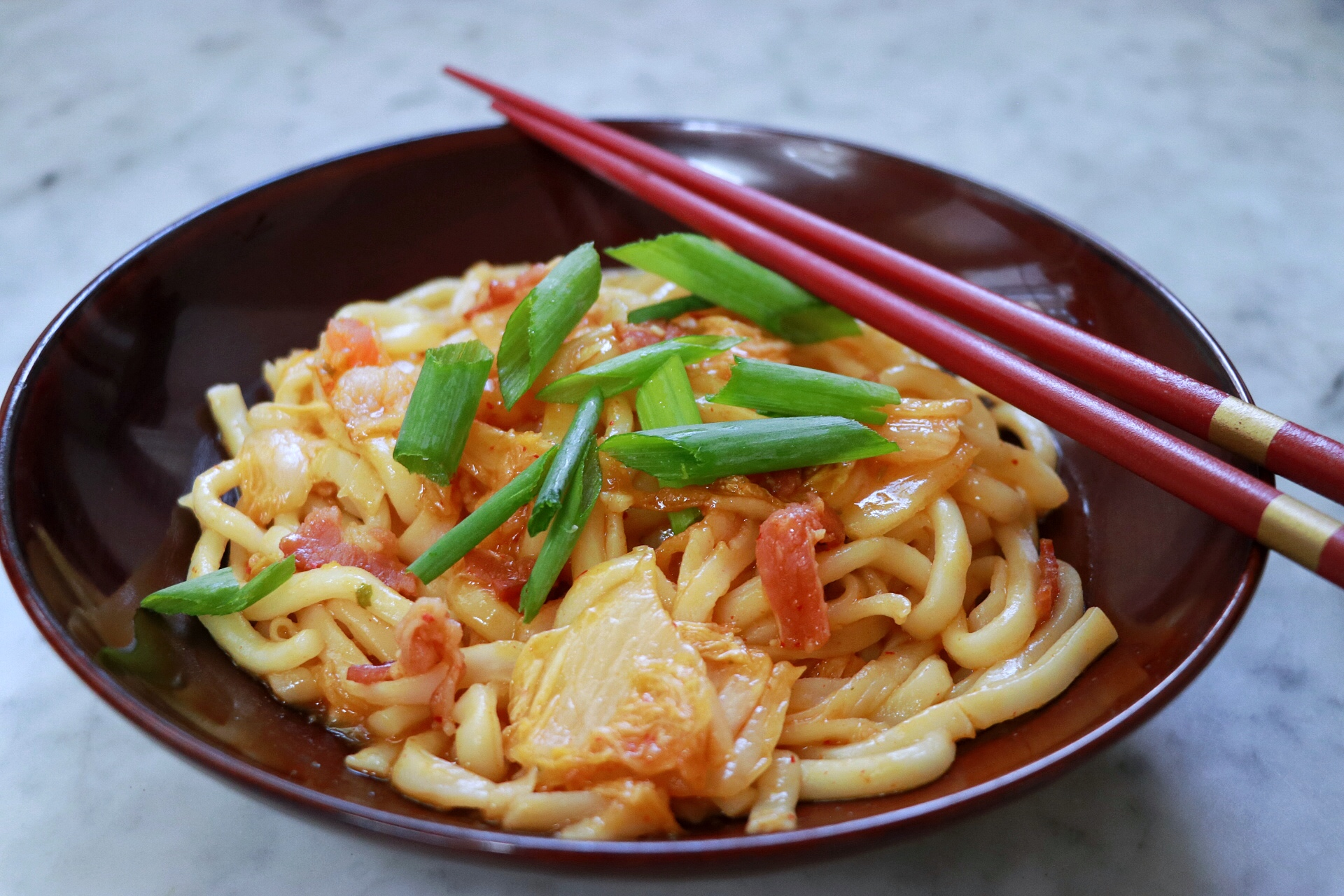 "Fresh udon noodles are stir-fried with bacon, kimchi, and garlic in a sweet and spicy sauce. ""This is a sweet, nutty, and spicy kimchi udon stir-fry your whole family will love -- and it takes mere minutes to make from start to finish!"" says chpmnk42. ""Top with cooked eggs and shredded nori if you like."""