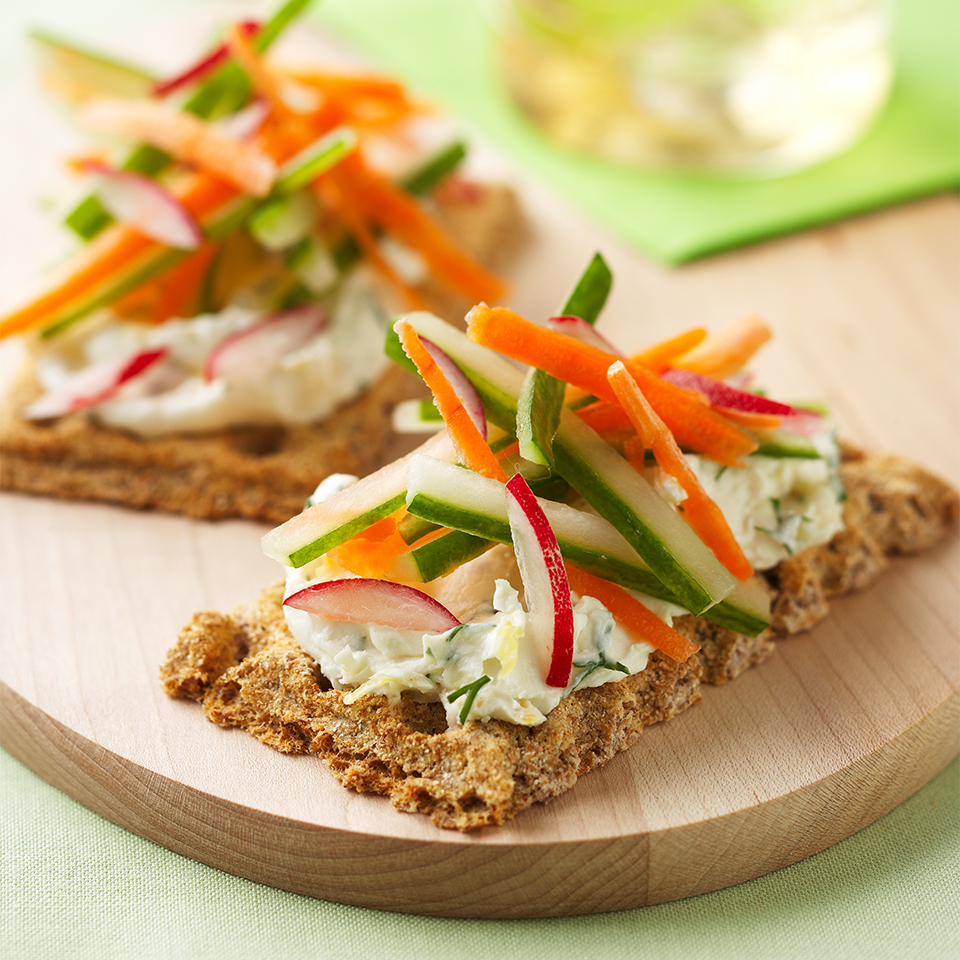 Rye crisps are topped with a light and creamy cheese spread flavored with lemon and served with colorful vegetables for a pretty, easy appetizer or small plate.