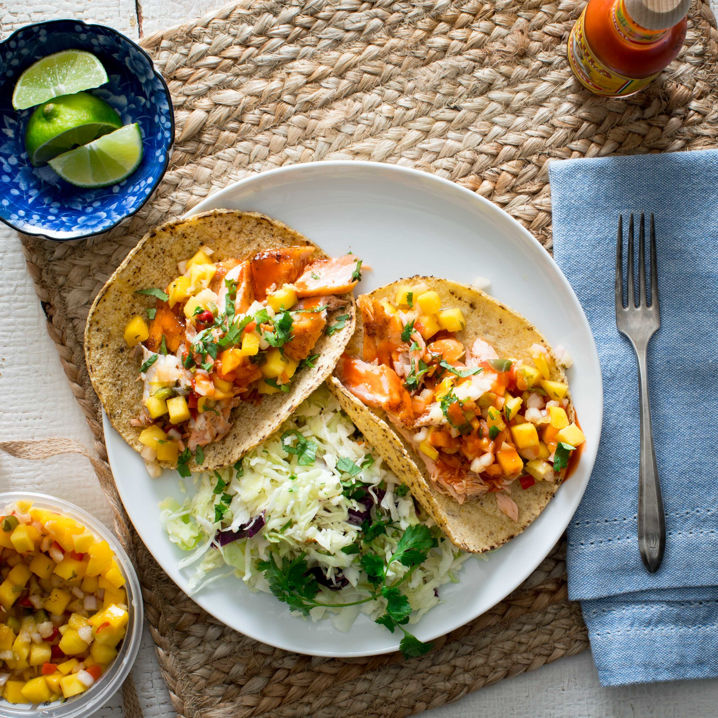 An easy-to-make slaw served on the side of these salmon tacos makes for a filling and fast weeknight dinner. If you prefer more heat in these fish tacos, simply add a pinch or two of chipotle chile powder or cayenne with the chili powder.
