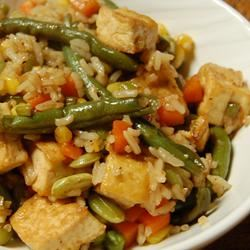 """This quick and easy recipe will have you drooling over this hearty main dish of lightly fried tofu, rich spices, and yummy vegetables,"" says deanne033. ""Lightly frying the tofu and veggies in mostly red wine vinegar rather than all oil cuts the calories down tremendously. Frozen or fresh vegetables work. I used a frozen mix-pack of green beans, diced carrots, corn, and soy beans. Goes great with rice."""