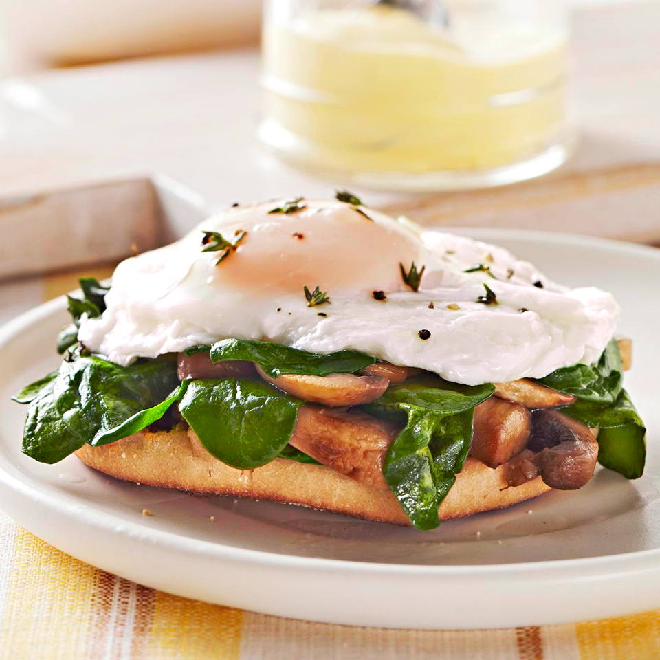You can feel good about eating this make-at-home version of eggs Benedict. We've replaced the ham with wilted spinach and golden brown sautéed mushrooms, and lightened up the sauce by using light sour cream and fat-free milk.