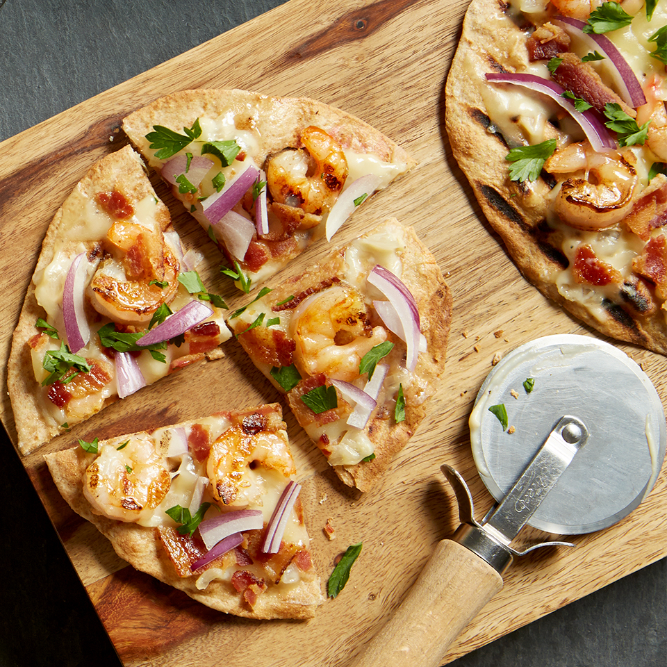 If you love shrimp Alfredo on pasta noodles, you'll really enjoy this pizza recipe. The Alfredo-based white sauce coats individual whole-wheat pizza crusts which are topped with grilled shrimp, bacon, and slices of red onion.
