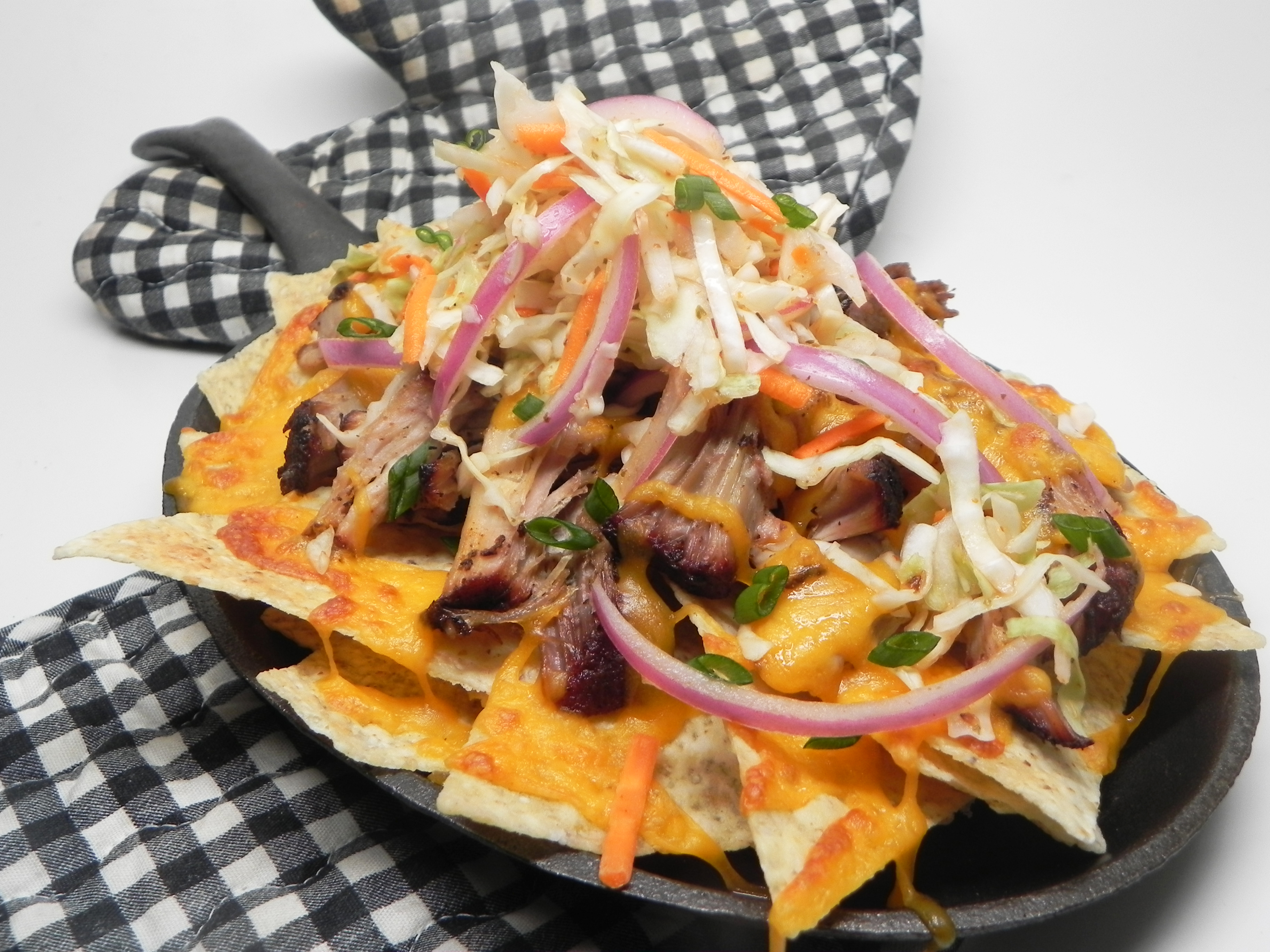 """""""Step up your nacho game this game day by turning leftover pulled pork into a sheet-full of goodness no one will be able to resist,"""" says Soup Loving Nicole. """"Garnish with pickled jalapeno slices, if desired."""""""